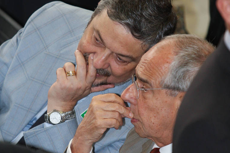 Palocci está à esquerda e Thomaz Bastos, à direita; com a mão encobrindo a boca, Palocci parece cochichar a Thomaz Bastos