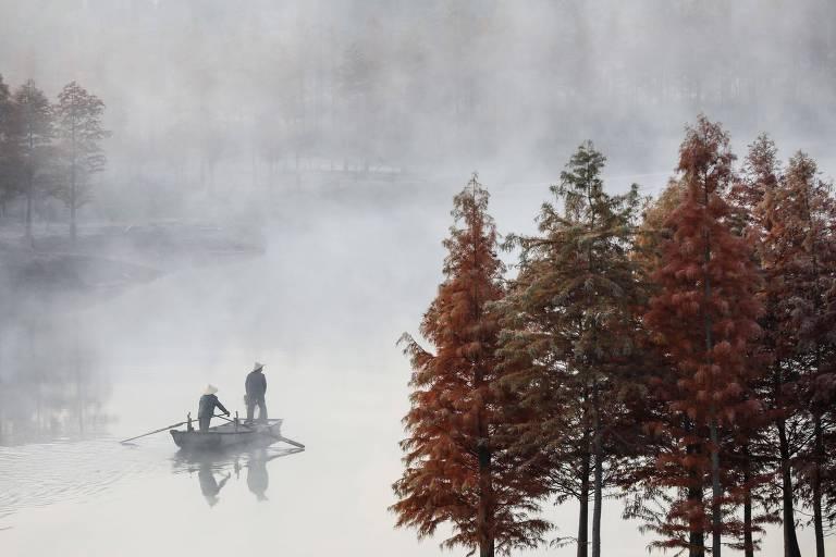 Duas pessoas andam em um mesmo barco num lago em dia de neblina. Há árvores em tons avermelhados no canto direito da imagem
