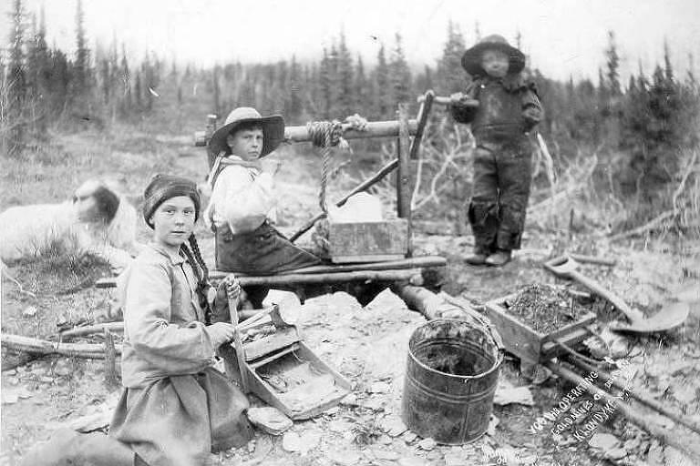 Três crianças trabalham em uma mina de ouro em Dominion Creek, no Canadá, em 1898