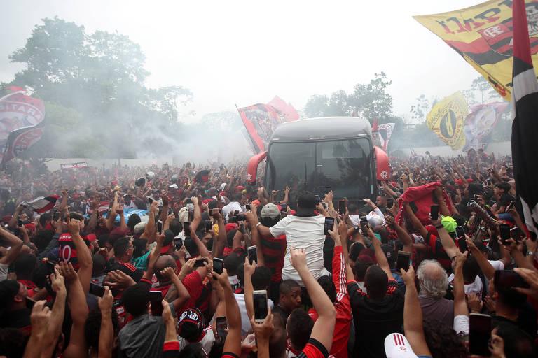 Ônibus do Flamengo é cercado por torcedores vestidos com uniforme do Flamengo, as pessoas vibram e erguem os braços, alguns carregam bandeiras, há fumaça de sinalizadores