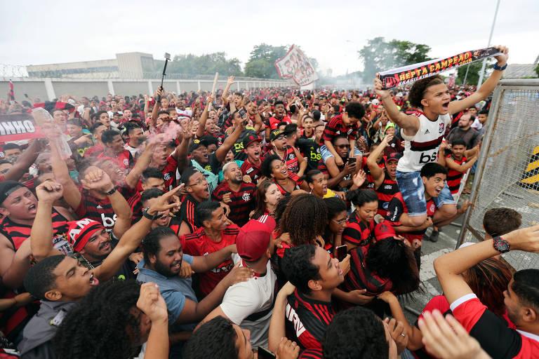 Em meio à multidão, torcedor rubro-negro exibe faixa de heptacampeão brasileiro na área externa do aeroporto
