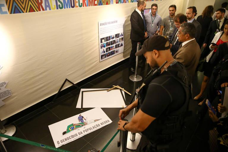 Placa quebrada com charge que fazia parte de exposição sobre Dia da Consciência Negra na Câmara