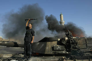 A militiaman loyal to Muqtada al-Sadr celebrates atop a burning American tank after it was destroyed - the crew escaped, according to the U.S. military - during clashes with American forces in the vast Sadr City neighborhood of Baghdad, Aug. 16, 2004. (Joao Silva/The New York Times)