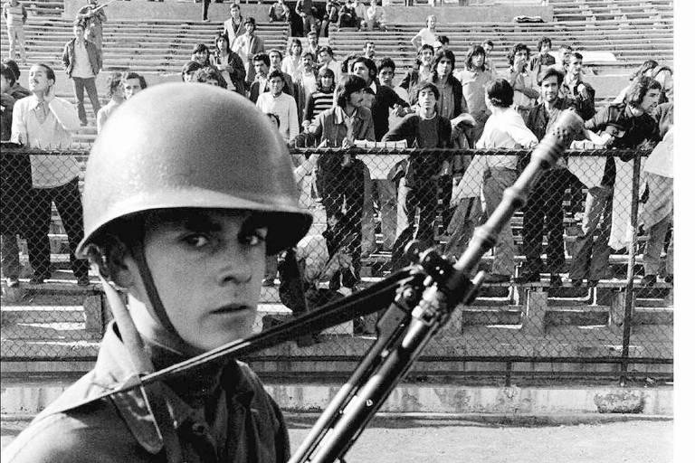 Soldado chileno com metralhadora e, ao fundo, torcedores nas arquibancadas do Estádio Nacional