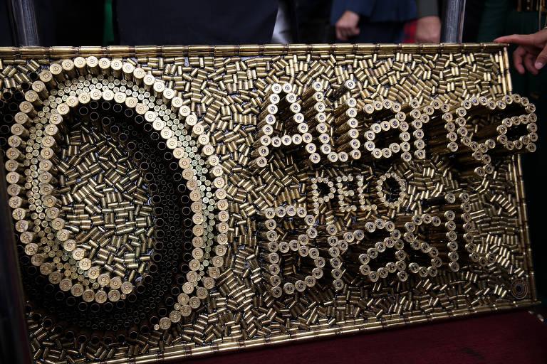 Obra feita de cartuchos de balas com nome e símbolo do partido Aliança pelo Brasil, lançado na última quinta (21)