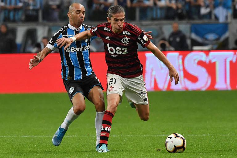 Filipe Luís protege a bola de Diego Tardelli contra o Grêmio, na semifinal da Libertadores