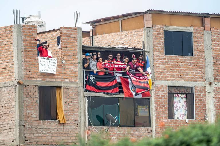 Torcedores do Flamengo assistem ao treino da equipe de uma casa nos arredores do CT da seleção do Peru, em Lima