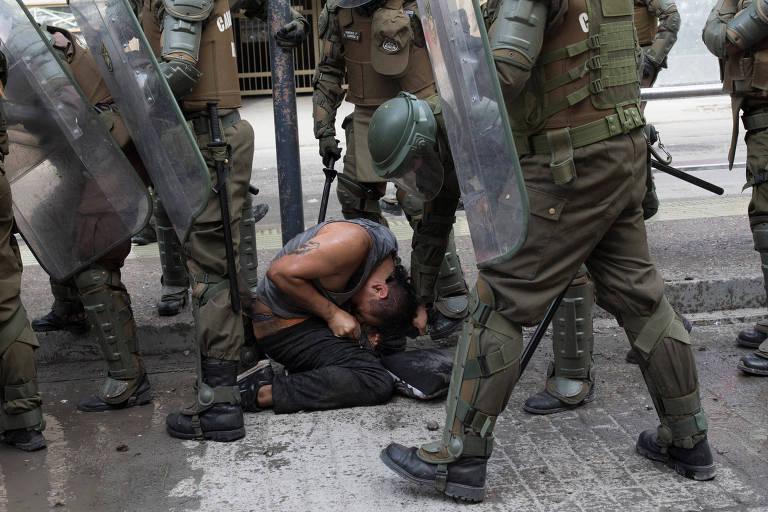 Policiais da tropa de choque puxam cabelo de manifestante enquanto ele é detido em Santiago, no Chile