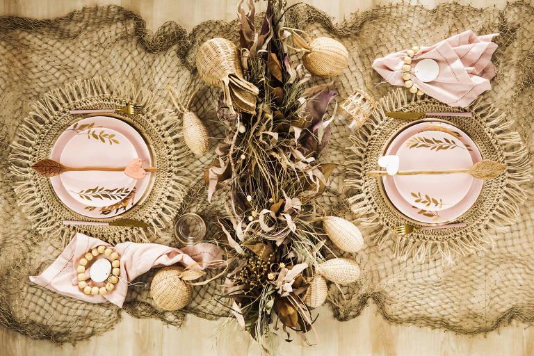 Mesa de natal decorada com rede de pesca, talheres e pratos cor de rosa