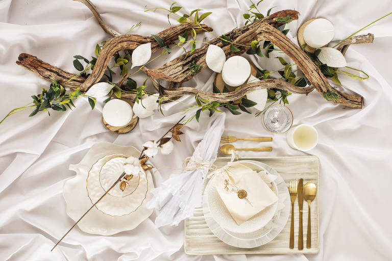 Mesa de natal de decoração branca com pratos, talheres, toalha de linho e arranjo de galhos secos