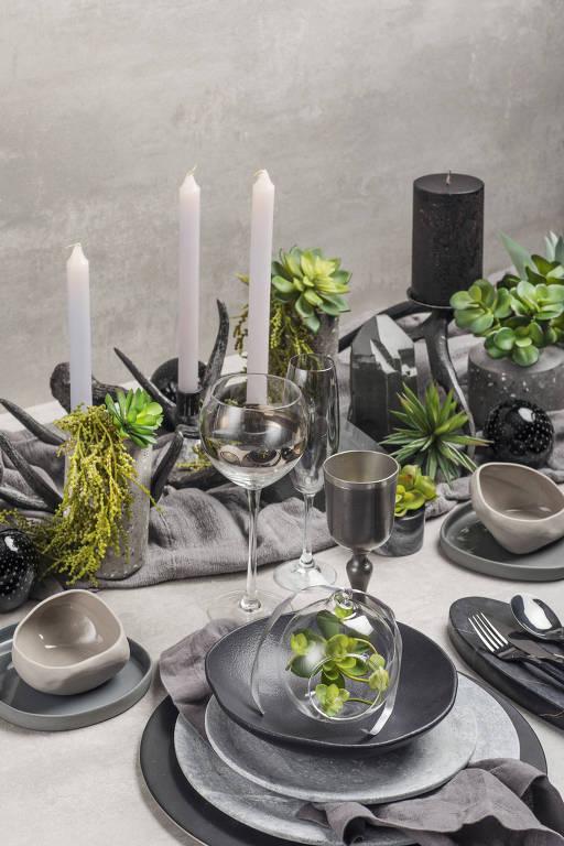 Mesa com decoração cinza, preta e plantas de tons escuros