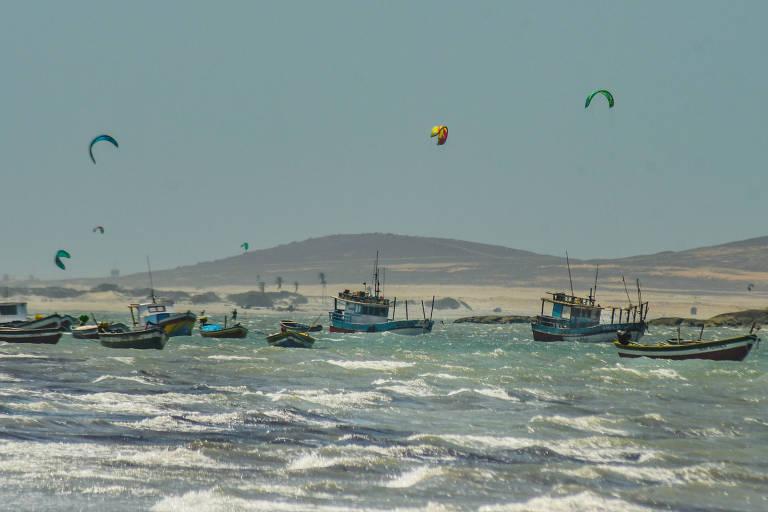 Mar com barcos de madeira e muitos paraquedas de kitesurf no céu