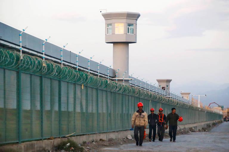 Operários caminham ao lado de cerca de arame farpado de um centro de internação