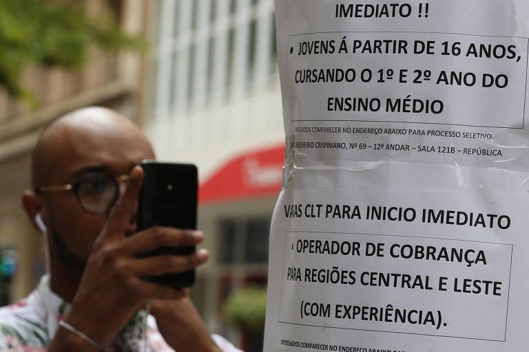 Na foto, alguns papéis com anúncios de vagas de emprego estão coladas em um poste. Em segundo plano, um homem fotografa uma das vagas com o celular