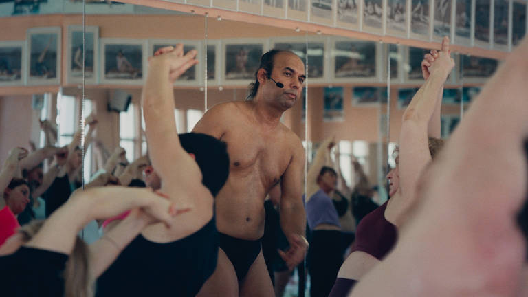 homem sobre pessoa em aula de ioga