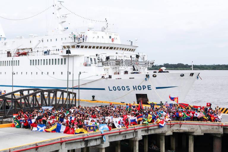 """Navio com os dizeres """"Logos Hope"""" ancorado diante de píer repleto de pessoas com badeiras de diversos países"""