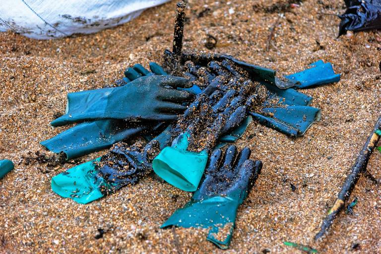 Luvas de proteção cobertas com óleo derramado na Praia de Busca Vida, em Camaçari, na Bahia, durante uma operação de limpeza em 3 de novembro de 2019