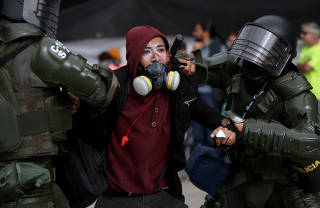 A demonstrator is detained by police officers during a protest at Bolivar Square as national strike continues in Bogota
