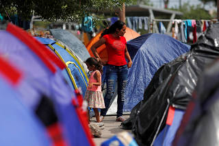 FILE PHOTO: Central American migrants are seen outside their tents in an encampment in Matamoros