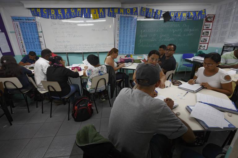 Sala de aula tem mesas rodeadas de adultos, escrevendo em cadernos