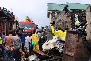 Rescuers and civilians gather at the site where a Dornier 228-200 plane operated by local company Busy Bee crashed into a densely populated neighborhood in Goma