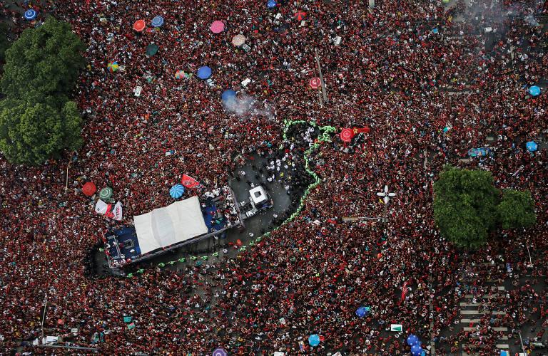 Veículo com os jogadores cercado por uma multidão com camisas do time, nas cores vermelho e preto