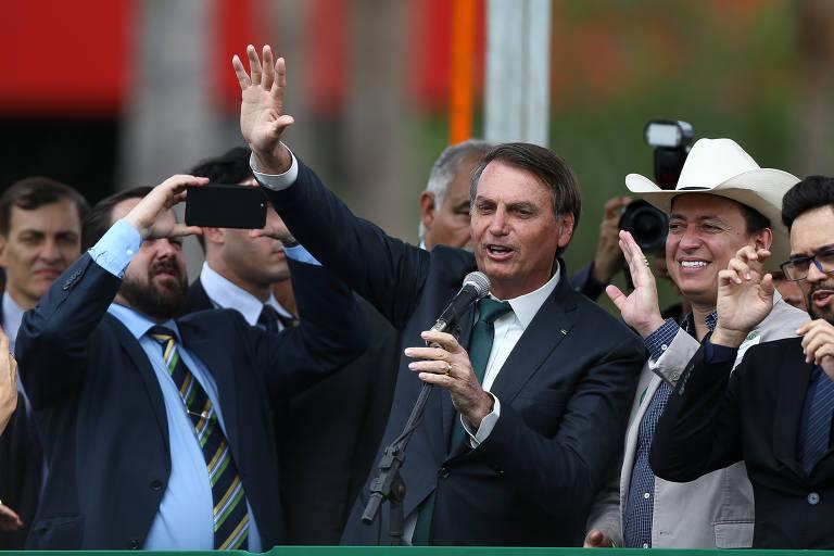 Jair Bolsonaro, de terno preto e gravata verde, discursa ao microfone. Ele segura um microfone com uma mão e seu outro braço está erguido