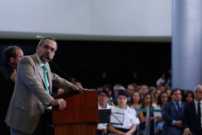 Homem de terno bege e gravata verde fala em um púlpito diante de sala com plateia cheia