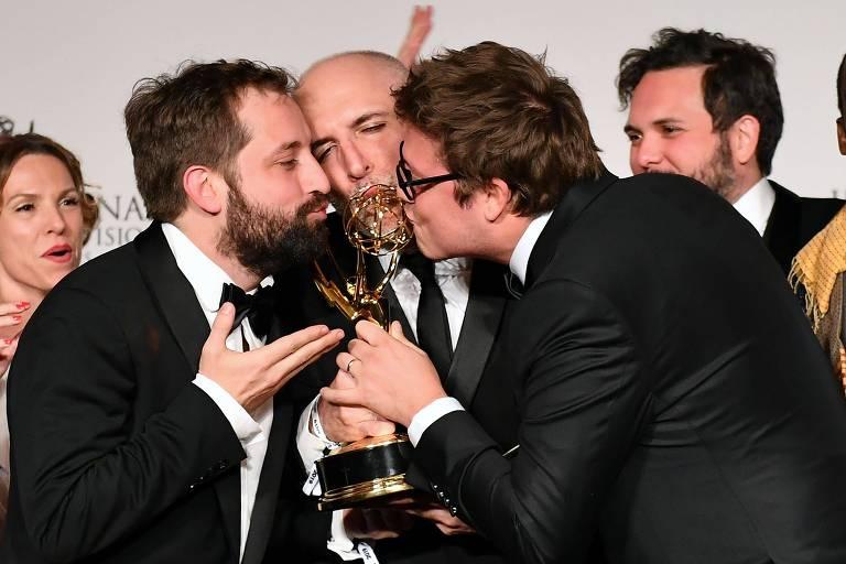 Três homens beijam troféu