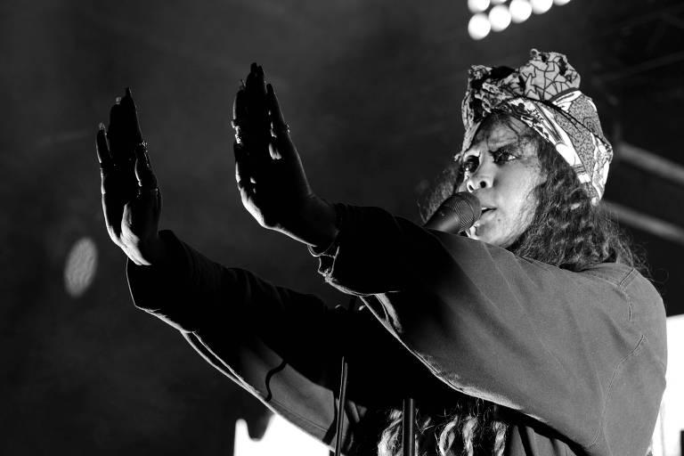Na imagem, Erykah Badu está de frente para o microfone com as mãos esticadas mostrando as palmas para a plateia