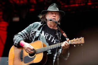 Canadian singer-songwriter Neil Young performs at the Orange Stage at the Roskilde Festival