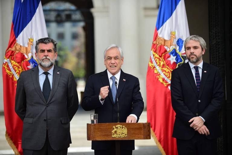 O presidente chileno Sebastían Piñera discursa ao lado do ministro de Interior e da Segurança, Gonzalo Blumel (dir.) e seu subsecretário, Robrido Ubilla (esq.), em Santiago