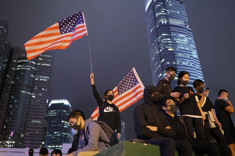 Manifestante com bandeira dos EUA durante protesto em Hong Kong