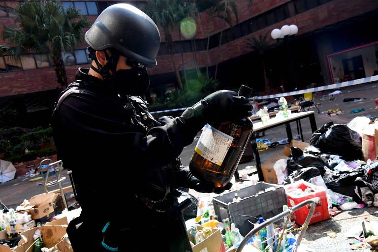 Policial recolhe produto químico encontrado na Universidade Politécnica, após a saída dos manifestantes