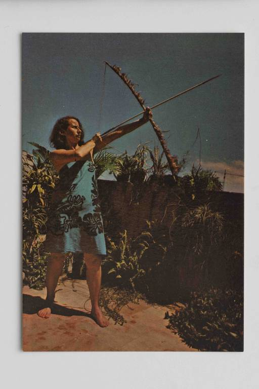 Anna Bella Geiger imita a pose de um indígena num postal em 'Brasil Nativo/Brasil Alienígena', obra de 1976-1977 exposta na mostra da artista no Masp