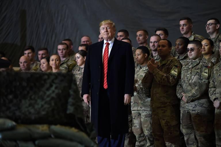 trump de terno e gravata vermelha em frente a militares vestidos com uniforme camuflado