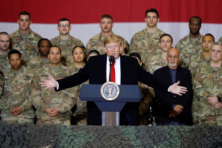 Presidente discursa, com os braços abertos; atrás dele há militares uniformizados perfilados