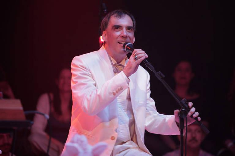 Arnaldo Antunes, vestido de branco, segura microfone em show