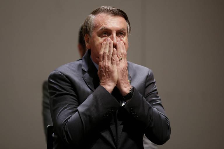 Bolsonaro com as mãos no rosto, encobre a boca