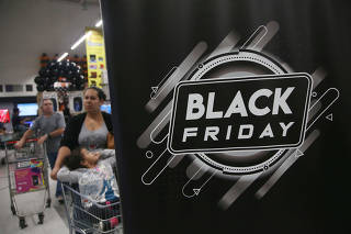 Shoppers push carts before making their purchase in a store during Black Friday in Sao Paulo