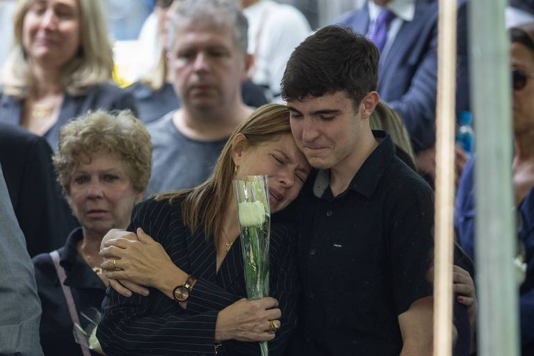 Rose Miriam é amparada pelo filho João Augusto no sepultamento do marido, o apresentador Gugu Liberato