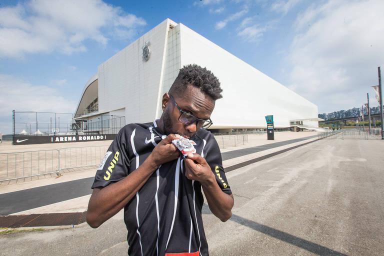 Lucas Conceição dos Santos beija a camisa do Corinthians em frente à arena de Itaquera, onde acompanha as partidas do time alvinegro na arquibancada ou à beira do gramado como gandula