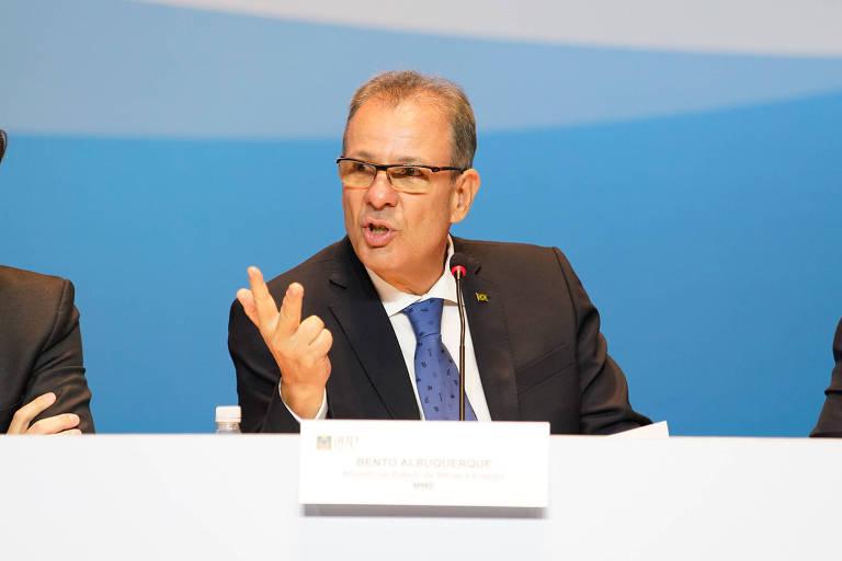 Na foto, Bento Albuquerque, ministro de Minas e Energia aparece sentado atrás de uma mesa, com um pequeno microfone, falando e gesticulando algo com a mão direita.