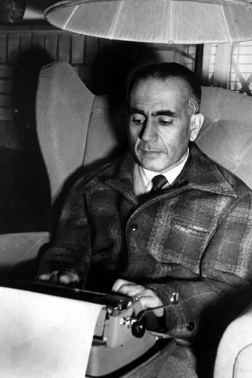 Erico Verissimo, retratado em 1951, quando trabalhava em 'O Tempo e o Vento'; na foto em preto e branco, vemos o escritor, um homem grisalho com a testa ampla, ficando calvo, e grossas sobrancelhas; ele veste uma roupa grossa de flanela xadrez e está sentado a uma poltrona, trabalhando na máquina de escrever que tem sobre as pernas