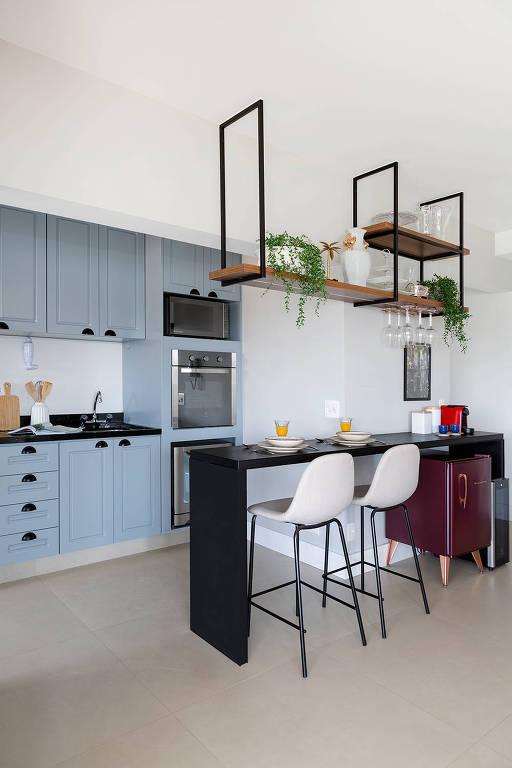 Nesta cozinha, a escolha foi por um tom suave de azul, que contrasta com o preto da bancada, no projeto do Oliva Estúdio de Arquitetura