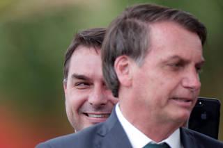 Brazil?s Senator Flavio Bolsonaro smiles near Brazil's President Jair Bolsonaro after the launch of a new political party, the Alliance for Brazil (APB) in Brasilia