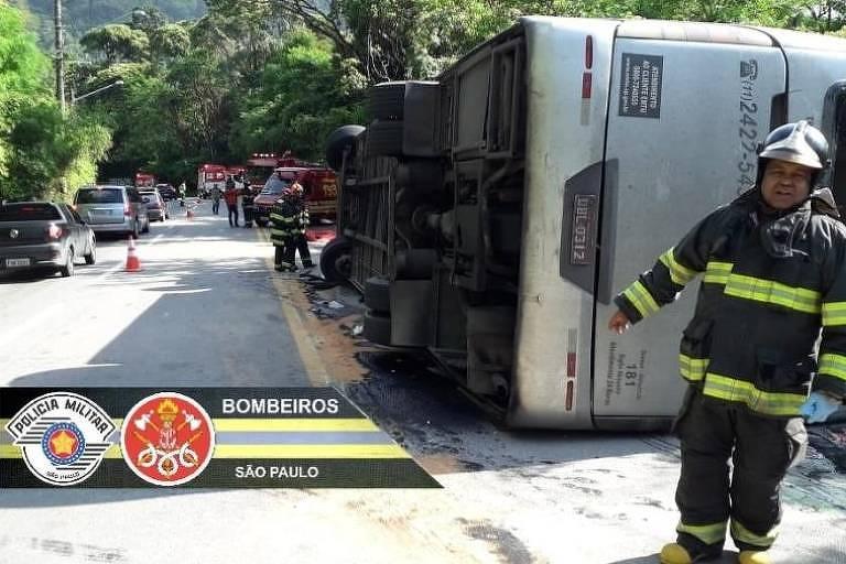 à direita, bombeiro traja uniforme de resgate preto com listras em amarelo florescente. Atrás dele está um ônibus tombado