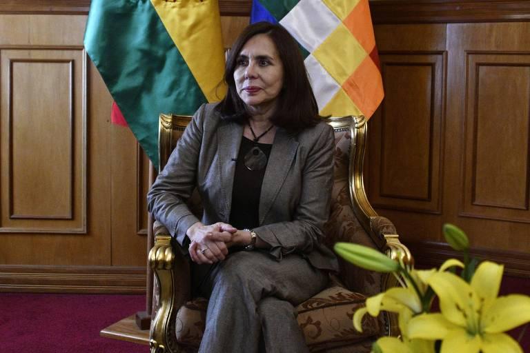 Mulher de meia idade está sentada com as pernas cruzadas. Usa terno, tem aparência formal, cabelos pretos.