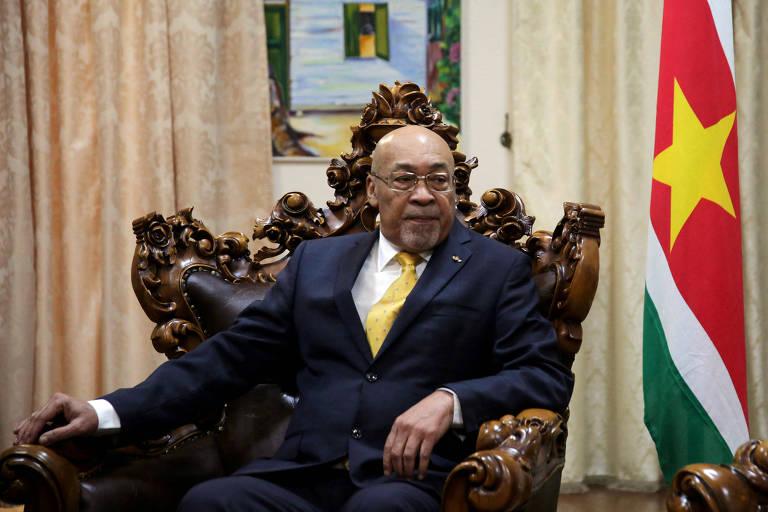 Presidente está sentado em uma poltrona de madeira e vestido com terno. Ao lado dele, a bandeira verde, amarela, branca e vermelha do Suriname.