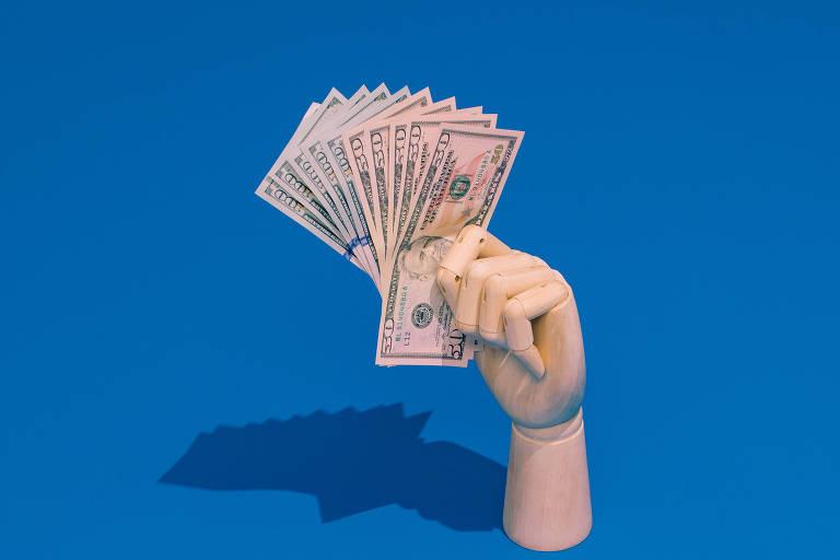Mão de madeira segura notas de dólar sobre fundo azul